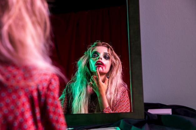 ハロウィーンの夜のために彼女の口紅を修正する女性