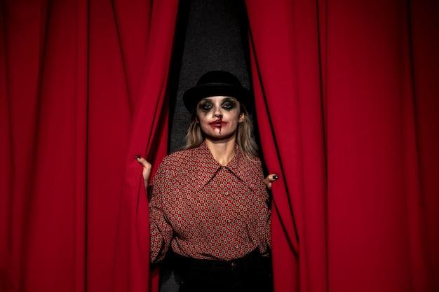 赤い劇場のカーテンを保持しているメイクアップ女性