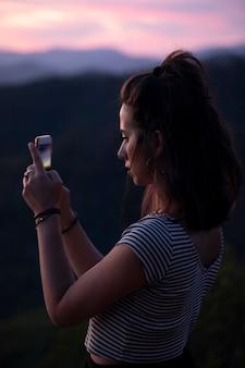 横向きの女性が彼女の電話で写真を撮る