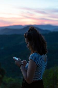 バックグラウンドで山と彼女の電話を見ている旅行者