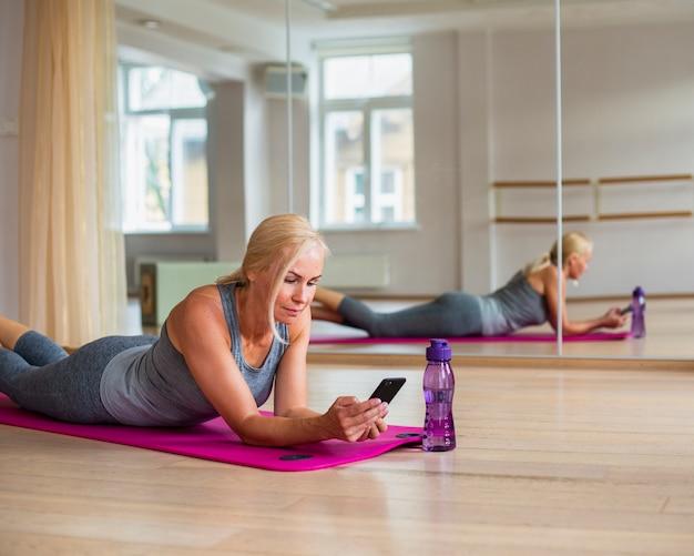 Женщина фитнеса проверяя ее телефон в спортзале