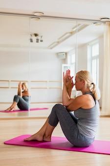 Пожилая женщина практикует медитацию