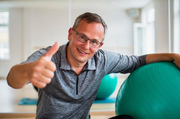 Положительный старший человек с шариком тренировки