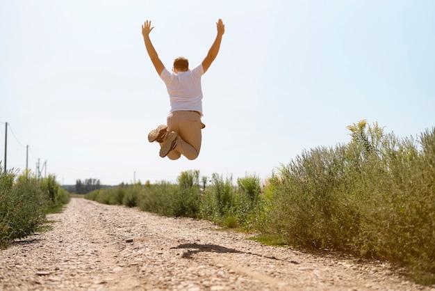 空気中のジャンプ若い男のロングショット