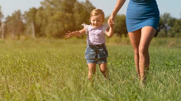 Молодая женщина, держась за руки с маленькой девочкой