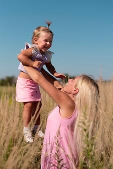 小さな女の子を保持している女性の正面図