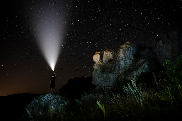自然の中で懐中電灯を持つ人