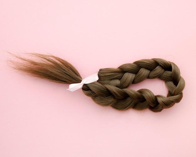 小さなピンクのリボンで編んだ髪