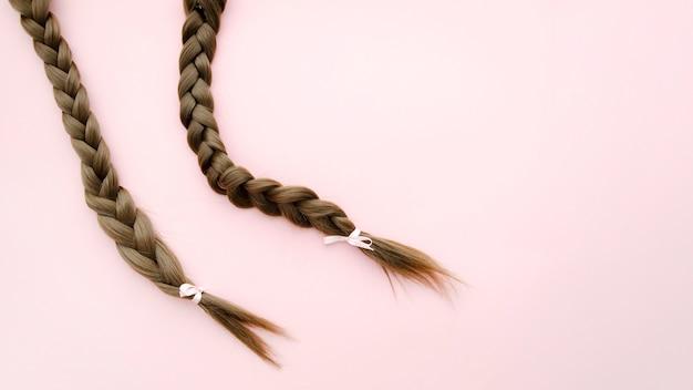 ピンクの背景のリボンと三つ編み