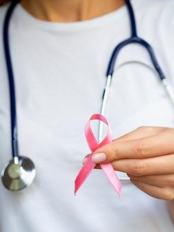 Крупным планом девушка с розовой лентой и стетоскоп