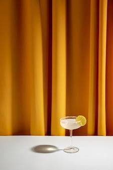 黄色のカーテンに対して白いテーブルに受け皿のグラスでライムカクテル