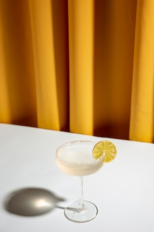 黄色のカーテンに対して白い机の上のシャンパン受け皿でライムカクテル