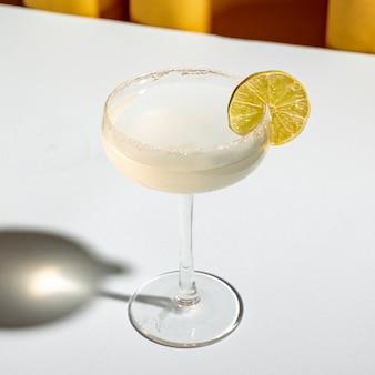白いテーブルの上の受け皿のガラスの端に塩と古典的なマルガリータカクテル