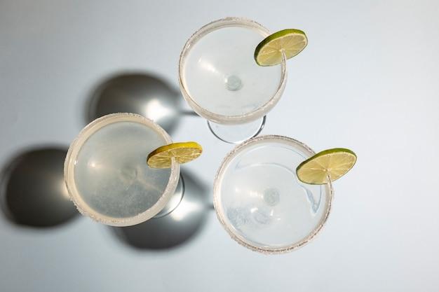 白いテーブルにライムと塩で自家製の古典的なマルガリータ飲み物の高角度のビュー