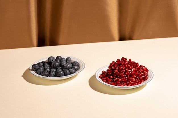 ザクロの種子と茶色のカーテンの近くの白いテーブルの上の皿にブルーベリー