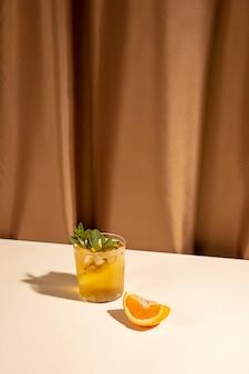 茶色のカーテンの近くの白いテーブルにオレンジスライスとカクテルドリンクグラス