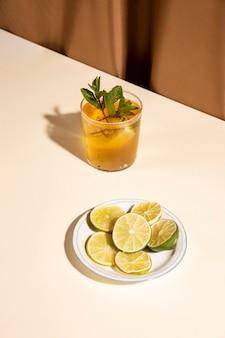 ミントの葉と白い机の上の皿にライムスライスのおいしい飲み物の立面図