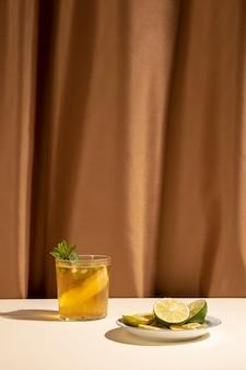 Вкусный коктейль с листьями мяты и ломтиками лайма на столе перед коричневой занавеской