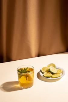 白い机の上のカクテルドリンクとレモンのスライス