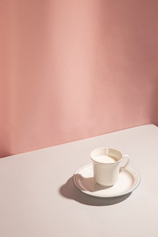 ピンクの背景のカップでミルクの高角度のビュー