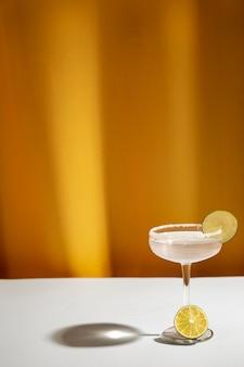 白いテーブルに塩味の縁とマルガリータカクテルグラスの影