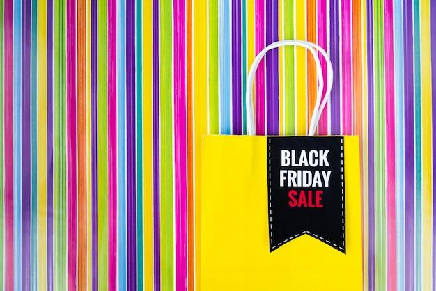 カラフルな背景に黒い金曜日ショッピングバッグ