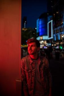 Мужчина опирается на стену и смотрит в сторону