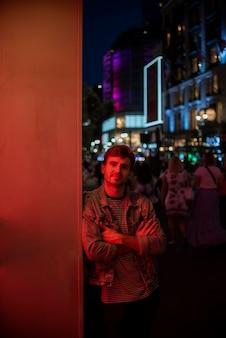 Человек, опираясь на стену и глядя на камеру