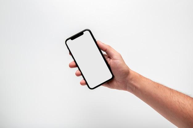 Рука держит телефон макет