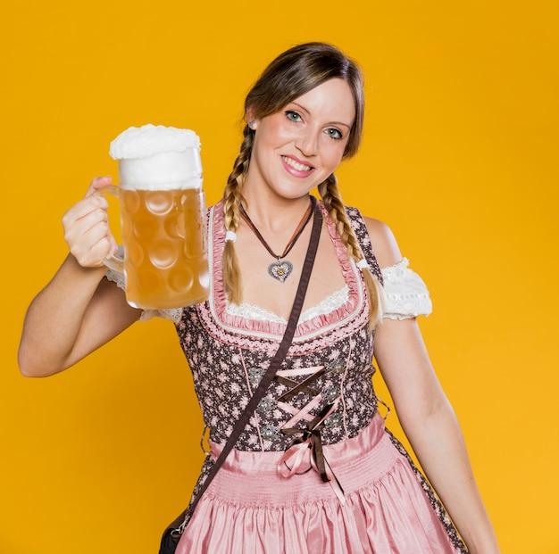 Положительная баварская женщина держа кружку пива