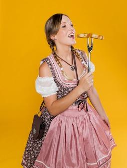 Праздничная женщина ест традиционную колбасу