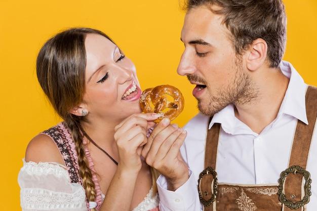 Баварские друзья пробуют вкусный крендель