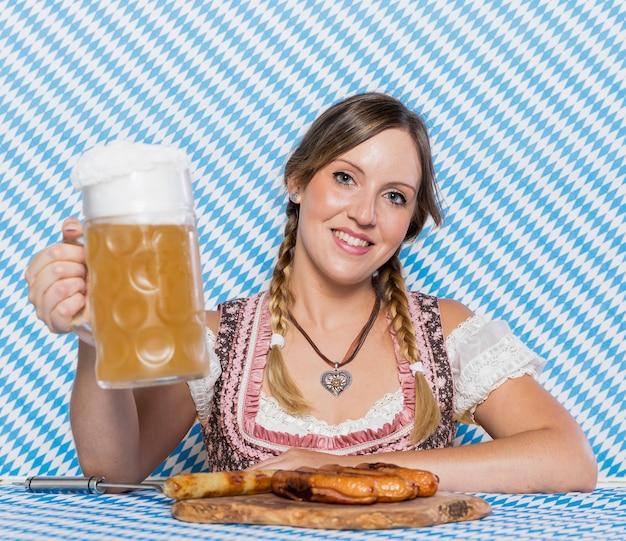 Улыбающаяся молодая девушка с баварскими закусками