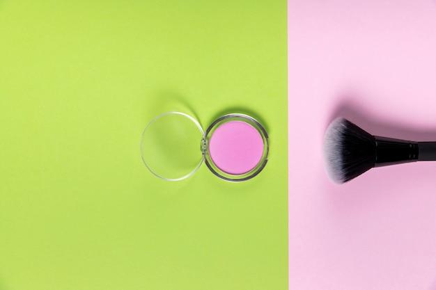 Вид сверху пудры и кисти на розовом и зеленом фоне
