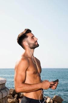 Молодой человек, наслаждаясь солнечным светом и слушать музыку