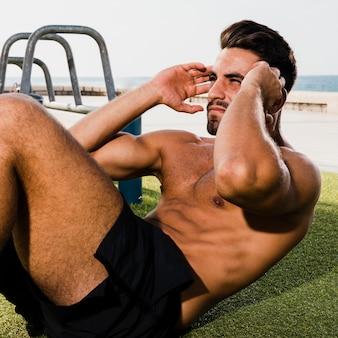腹筋運動をしているクローズアップの若い男