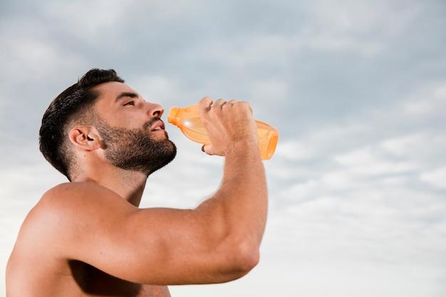 ハンサムな男の朝のスポーツの後の水分補給