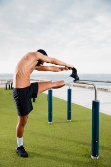 運動選手の男はトレーニングの前にウォームアップ