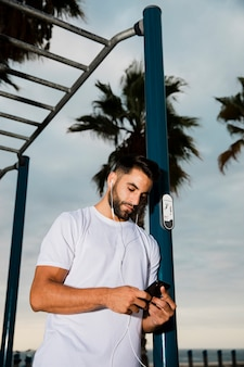 トレーニングの後の携帯電話で音楽を再生するハンサムな男