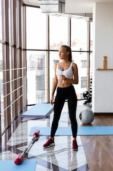 Женщина увлажняет после тренировки