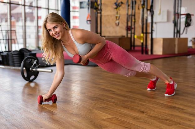 Женщина делает упражнения с весами