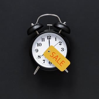販売サインと黒の目覚まし時計