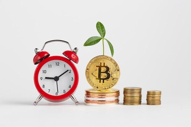 目覚まし時計の横にあるビットコインの山