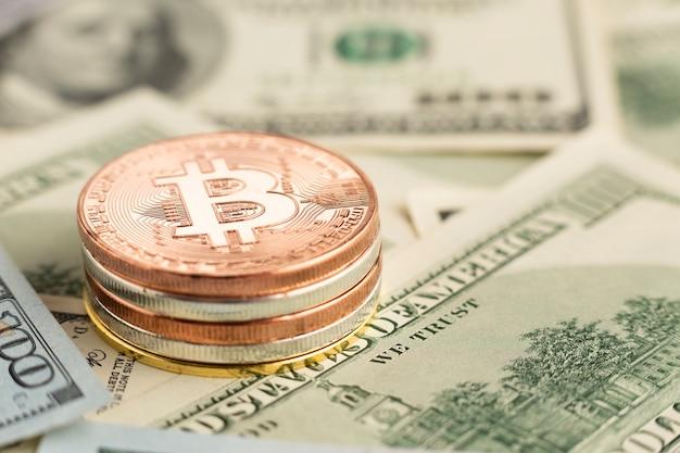 Куча биткойнов крупным планом на вершине банкнот