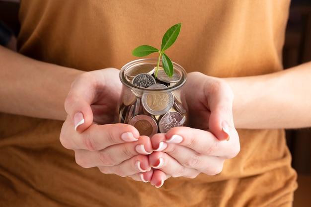 Лицо, занимающее банку монет с растением