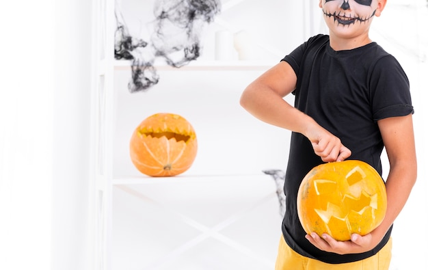 Страшный мальчик держит резную тыкву на хэллоуин