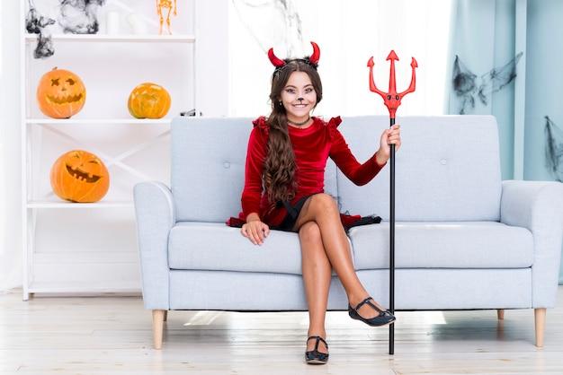 Девушка в полный рост с рогами дьявола и трезубцем на хэллоуин