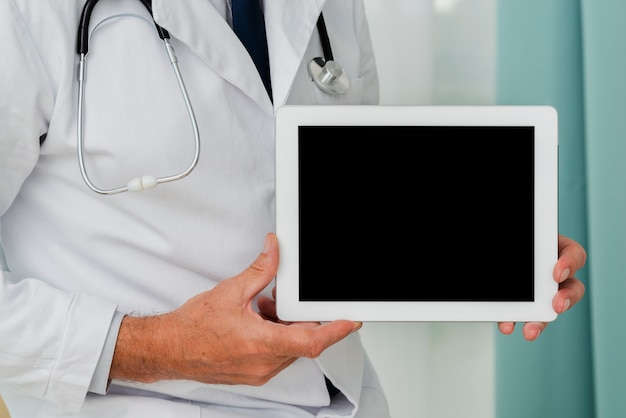 タブレットのモックアップを保持している医者のクローズアップ