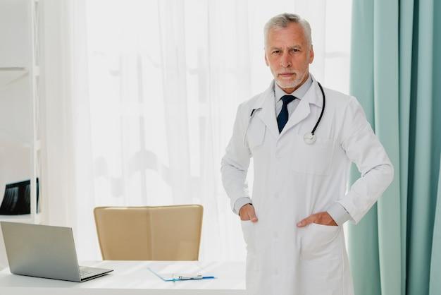 ポケットに手で机に立っている医者