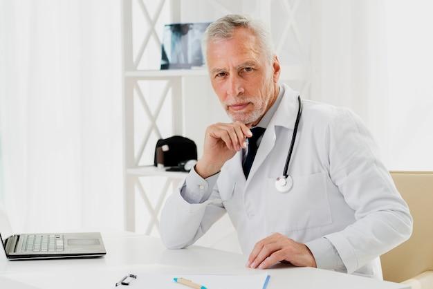 Доктор за столом с рукой на подбородке